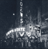 "<p>Joe Di Pesa created a patriotic front with great marquee topper (seen better in the next photo) by the Loew's State Theatre for ""Submarine"" in 1928. Crowds are seen here.</p>"