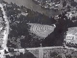 <p>An aerial view of the Starlite Drive-In on the corner of Norwell Drive and Departure Bay Road in the Departure Bay area of Nanaimo, taken circa 1966-67. The southern end of Long Lake is to the north of the drive-in, while construction of the then-new Wellington Secondary School (which took place around the time this photo was taken) is in its early stages on the right of the photo. The drive-in operated only a few more years after the photo was taken, as it closed after the 1973 season and its site was redeveloped for retail, residential and institutional use.</p>