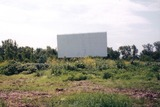 <p>Went back in 1995 and shot this photo of the main screen at the drive-in.  The concession stand walls were still up, but mostly bulldozed.  The layout of the drive-in was still apparent at that time.  The last films I saw at the Starlite was House on Haunted Hill and Lawrence of Arabia.  It was strange seeing epic films on the big screen and the sound coming out of a two-inch speaker. As the late Jean Shepherd (Christmas Story author et al) noted: There's something less than awe-inspiring at the drive-in when the voice of God in the Ten Commandments is an anemic squeeky chirp…</p>