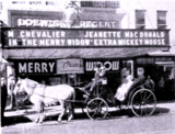 """<p>Sam Gilman, manager of the Loew's Regent Theatre in Harrisburg goes with a 75-year old carriage for """"The Merry Widow"""" playing there in 1934.</p>"""