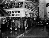 """<p>GONE WITH THE RAIN – A crowd gathers in front of the Loew's State Theatre in Houston on a rainy day in February, 1942 to see GONE WITH THE WIND.</p>                            <p>The film, which was originally premiered on December 15, 1939, was the top grossing film of thye year and won eight Academy Awards. In 1942, the producer, Davis O. Selznick liquidated his company for tax reasons, and sold his share in Gone with the Wind to his business partner, John Whitney, for $500,000. In turn, Whitney sold it on to MGM for $2.8 million, so that the studio owned the film outright. MGM immediately re-released the film.""""               Photo credit: Dolph Briscoe Center for American History.</p>"""