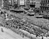 <p>View of the RKO Mayfair and the RKO Palace from Duffy Square during a parade in the 1940s</p>