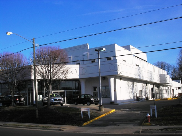 The original structure is the two story building. The outlying trimming was added during the conversion from a theatre to an automotive dealership.