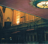 <p>This was taken from underneath the balcony, shot towards the front of the house. The place smells musty but appears to be in pretty good shape. The main floor has been leveled off for use as a dance floor and for parties. The upper level seats are still in place. This is a very THIN auditorium.</p>