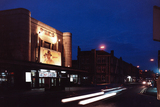 <p>This impressive night shot shows the building beautifully lit up at night in 1989.               This was before the cinema changed to a read-o-graph, the banner advertising the films above the doors was hand painted!</p>