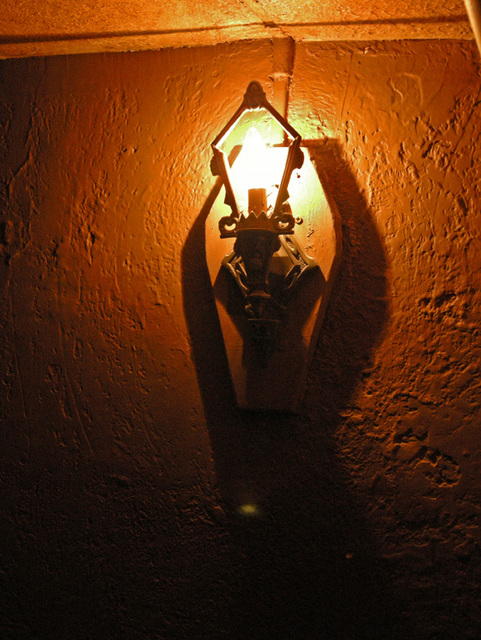 wall sconce in stairwell leading to balcony