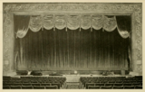 <p>Oxford Theatre, Philadelphia, PA in 1928 – Proscenium arch and drapes. An orange valance frames curtains of the same fabric in a brick colour, with a foot trimming of heavy fringe.</p>