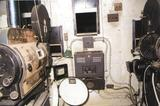 "<p>In the center of the front of the booth wall, is the RCA tube type sound system in that black cabinet with the knob on it. The projection booth ""porthole shutter"" system still works. The booth is completely lined in metal and is fire proof.</p>"